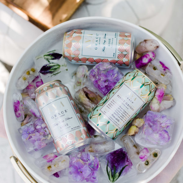 Can of AVA Grace wines in an ice bucket with beautiful floral ice cubes.
